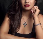 Beautiful woman wearing cross Necklace. Beautiful woman wearing black jewels with a cross necklace and diamond bracelet. Perfect model for jewelry stores royalty free stock image