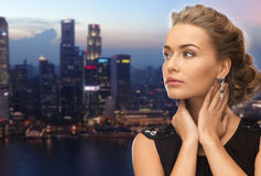 Beautiful woman wearing earrings over evening city Royalty Free Stock Photography