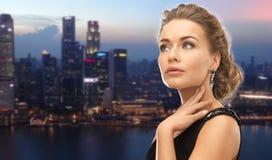 Beautiful woman wearing earrings over evening city Stock Photos