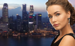 Beautiful woman wearing earrings over evening city Royalty Free Stock Photos