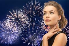 Beautiful woman wearing earrings over firework Stock Photo