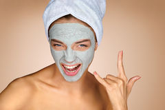 Beautiful woman wearing a facial mask and making rock hand gesture Royalty Free Stock Photography