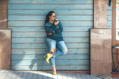 Plus size woman walking on the city street. Beautiful woman wearing fall sweater, ripped jeans and colorful shoes drinking take away coffee standing against cafe Royalty Free Stock Image