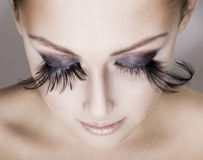 Beautiful woman  wearing false eyelashes. Closeup of young beautiful woman  wearing false feather eyelashes. Woman's face looking down Stock Photography