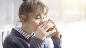 Beautiful woman wearing a gray sweater is enjoying her tea in a cafe and daydreaming. Portrait shot Stock Images