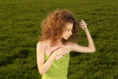 Beautiful woman wearing a green dress and posing in the fields Royalty Free Stock Images