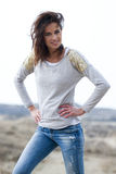 Beautiful woman wearing grey shirt and jeans in the dunes. Beautiful young woman wearing a grey shirt and jeans posing in the dunes royalty free stock photos