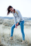 Beautiful woman wearing grey shirt and jeans in the dunes. Beautiful young woman wearing a grey shirt and jeans posing in the dunes royalty free stock images