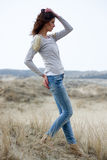 Beautiful woman wearing grey shirt and jeans in the dunes. Beautiful young woman wearing a grey shirt and jeans posing in the dunes Royalty Free Stock Image