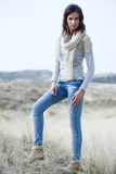 Beautiful woman wearing grey shirt and jeans in the dunes. Beautiful young woman wearing a grey shirt, a white scarf and jeans posing in the dunes royalty free stock images