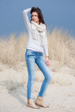Beautiful woman wearing grey shirt and jeans in the dunes. Beautiful young woman wearing a grey shirt, a white scarf and jeans posing in the dunes stock image