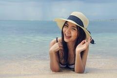 Beautiful woman wearing a hat lying on the beach royalty free stock photo