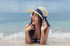 Beautiful woman wearing a hat lying on the beach Royalty Free Stock Photo