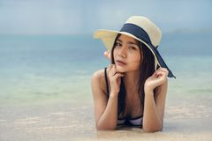 Beautiful woman wearing a hat lying on the beach Stock Images