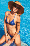 Beautiful woman wearing a hat and sunglasses, enjoying the pool Royalty Free Stock Photo