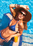 Beautiful woman wearing a hat and sunglasses, enjoying the pool Stock Image
