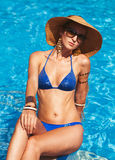 Beautiful woman wearing a hat and sunglasses, enjoying the pool Royalty Free Stock Image