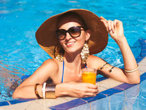 Beautiful woman wearing a hat and sunglasses, enjoying the pool Stock Photo