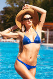 Beautiful woman wearing a hat and sunglasses, enjoying the pool Royalty Free Stock Images
