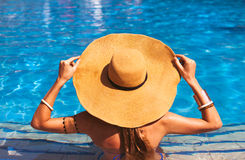 Beautiful woman wearing a hat and sunglasses, enjoying the pool Stock Photography