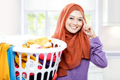 Beautiful woman wearing hijab carrying laundry basket with hand Stock Image