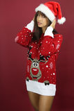 Beautiful woman wearing a kitsch Christmas sweater. Over a red background royalty free stock photo