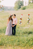Beautiful woman wearing lilac dress wreath and handsome man in peach shirt standing near swing outdoors Royalty Free Stock Image