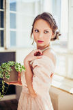 Beautiful woman wearing long dress holding house plant. Royalty Free Stock Photos