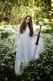 Beautiful woman wearing a long white dress holding a sword Royalty Free Stock Photos