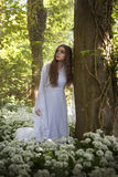 Beautiful woman wearing a long white dress leaning on a tree Royalty Free Stock Image