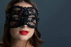 Woman wearing masquerade mask against black background. Beautiful woman wearing masquerade mask against black background Royalty Free Stock Photo