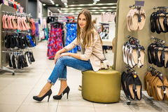 Beautiful woman wearing new high heels shoes at shop. Young and beautiful woman wearing new high heels shoes at shop stock photo