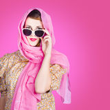 Beautiful woman wearing pink headscarf fashion. Feminine portrait of a beautiful young woman wearing sun protection headscarf and sunglasses. On pink background Royalty Free Stock Photos
