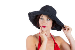 Beautiful woman wearing red bikini and black hat in deep thought Royalty Free Stock Photo
