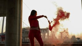 Elegant girl in red costume dancing with red smoke near old constructions. Beautiful woman wearing red costume is dancing at the sunset background with red smoke stock video footage