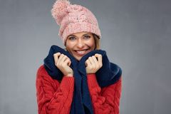 Beautiful woman wearing red knitted sweater. Portrait isolated on gray wall back Royalty Free Stock Image
