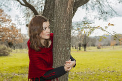 Beautiful woman wearing red wool poncho hiding behind a tree. Li Royalty Free Stock Photo