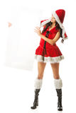 Beautiful woman wearing santa clothes. Santa woman holding white empty banner on the right, looking at it Stock Image