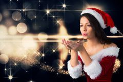 Beautiful woman wearing santa costume blowing a kiss against digitally generated christmas backgroun Stock Photography
