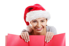 Beautiful woman wearing santa hat, holding shopping bag. Royalty Free Stock Photography