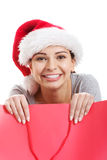 Beautiful woman wearing santa hat, holding shopping bag. Royalty Free Stock Photos