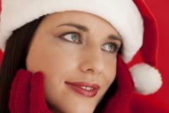 Beautiful woman wearing santa's hat. Close-up of a beautiful woman in santa's hat, on red background Royalty Free Stock Photos