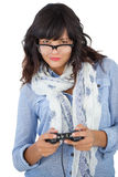 Beautiful woman wearing scarf and glasses playing video games Stock Photos