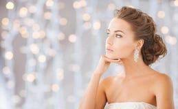 Beautiful woman wearing shiny diamond earrings Stock Photo