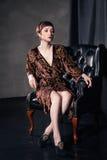 Beautiful woman wearing short dress sitting in Stock Image