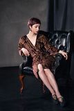 Beautiful woman wearing short dress sitting in Royalty Free Stock Image