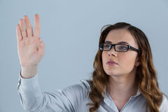 Beautiful woman wearing spectacles pretending to touch an invisible screen Royalty Free Stock Photos