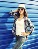Beautiful woman wearing a straw hat, sunglasses and checkered shirt. In city Stock Photo