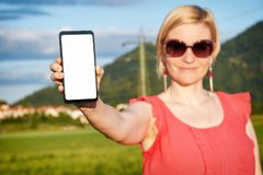 Beautiful woman wearing sun glasses while holding in hand a smartphone royalty free stock image