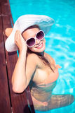 Beautiful woman wearing sunglasses and straw hat leaning on wooden deck by poolside Stock Images